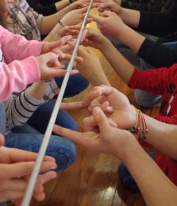 Teambildungsspiel, bei dem eone leichte Stange von vielen Fingern getragen wird